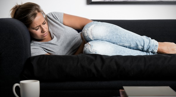 Woman lying on a couch with pain in her stomach
