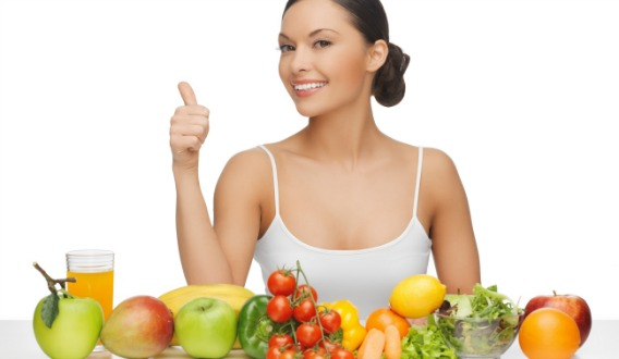 woman gives thumbs up with lot of fruits and vegetables
