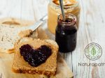Homemade peanut butter and heart shaped jelly sandwich on wooden background