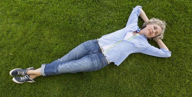 happy middle aged woman laying on the grass-630