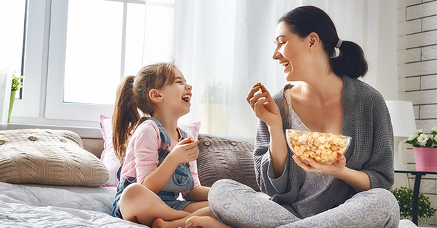 a girl and her mom eating popcorn-630