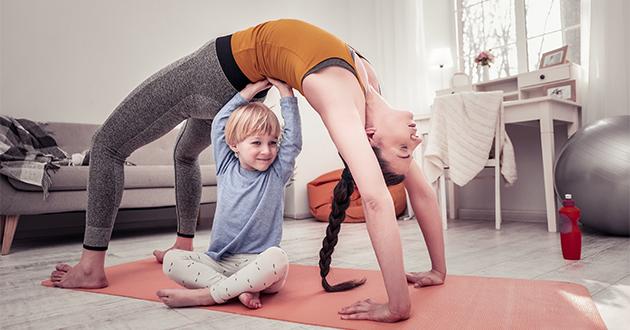 kid helping mom do yoga-630