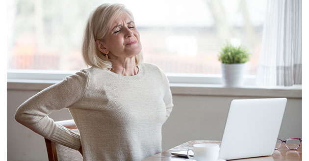 middle age woman with backpain sitting at the desk-630