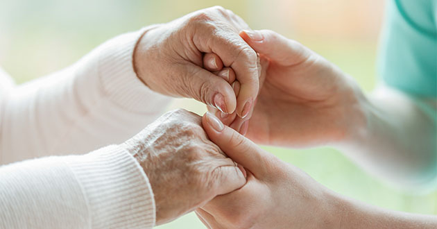 young woman holding hands of elderly-630